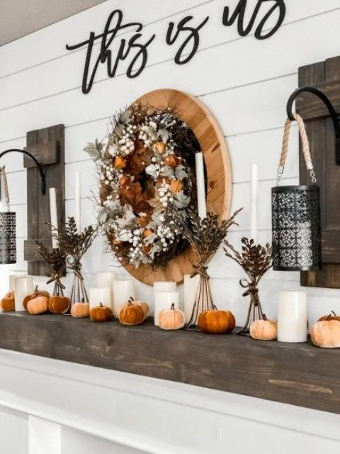 farmhouse fall mantel styling with faux pumpkins, pillar candles, branches in bottles and a wreath of leaves, blooms and berries