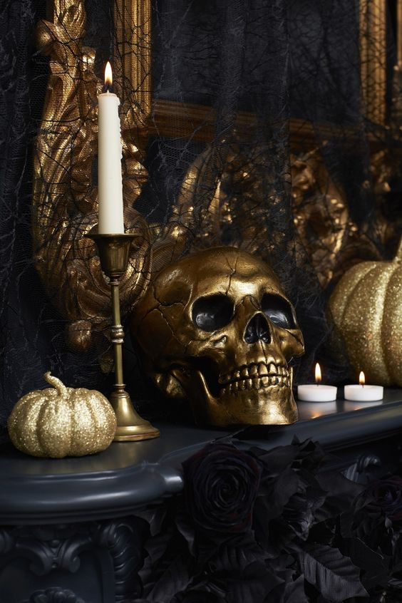glam black and gold Halloween decor with gold glitter pumpkins, a gold skull, gold candlesticks and white candles, faux black blooms