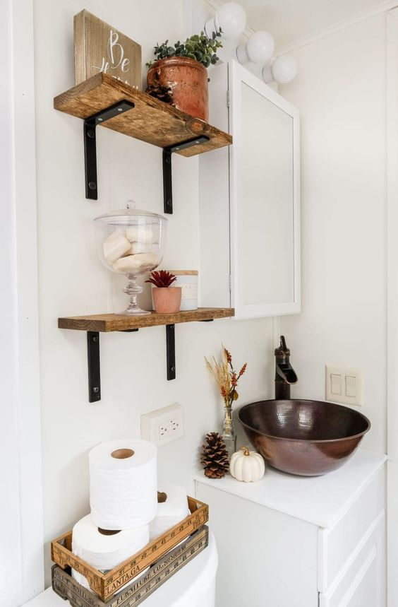 lovely and cozy bathroom styling with a pumpkin, a pinecone, dried flowers and grass in a bottle, some potted plants and pinecones