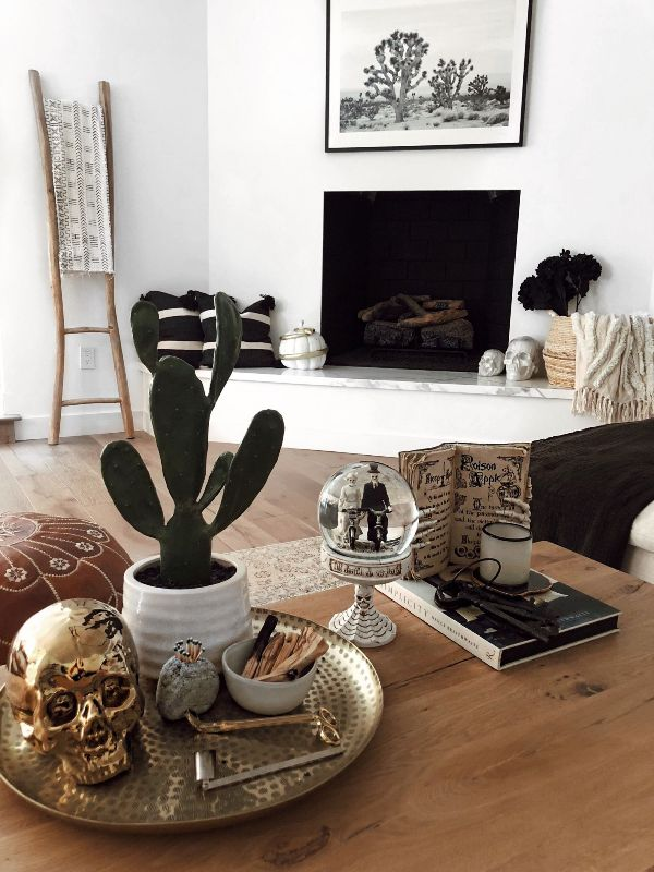 lovely modern Halloween decor with skulls, a scary globe, a witches' book and skeleton hands plus black blooms