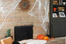 modern Halloween decor done with pumpkins and lights next to the fireplace, with spider web and a black pillow is simple and stylish