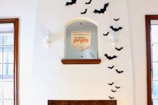 modern Halloween decor with a fireplace filled with pumpkins and black paper bats is a lovely idea for the flal