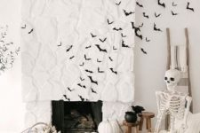 modern Halloween decor with black paper bats, white pumpkins stacked, a skeleton in a rocker, a black chandelier with a blackbird and some wheat