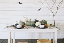 modern farmhouse Halloween decor with pumpkins on the table, tree stumps, branches, black bats and pumpkins on the floor
