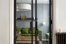 narrow black frame glass doors separate the spaces delicately and highlight the modern style of the apartment