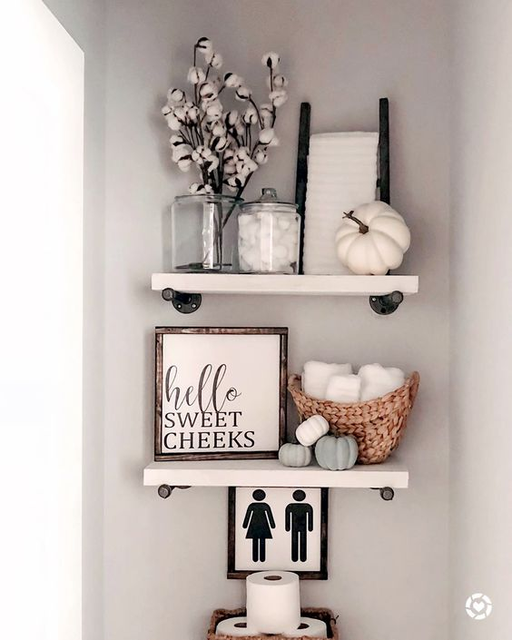 open shelving with cotton branches, lots of faux pumpkins and a sign is a cool idea for a rustic bathroom in the fall