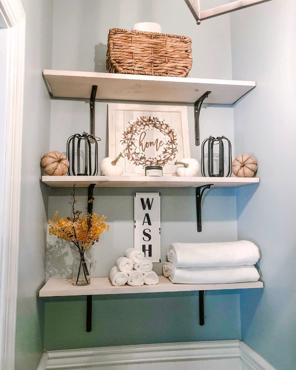 open shelving with faux pumpkins, bold branches, a cool cotton sign and fluffy white towels is a great idea for the fall