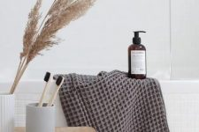 pampas grass in a neutral vase and some fluffy and cozy towels will make your bathroom feel more autumnal and cozy