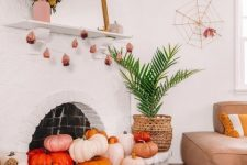 pink, red and orange pumpkins in the fireplace and around it and a mini pumpkin garland plus a spiderweb for modern Halloween decor