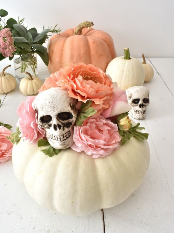 pretty Halloween decor of a white pumpkin, pink faux blooms and skulls is a lovely idea for a pastel Halloween party