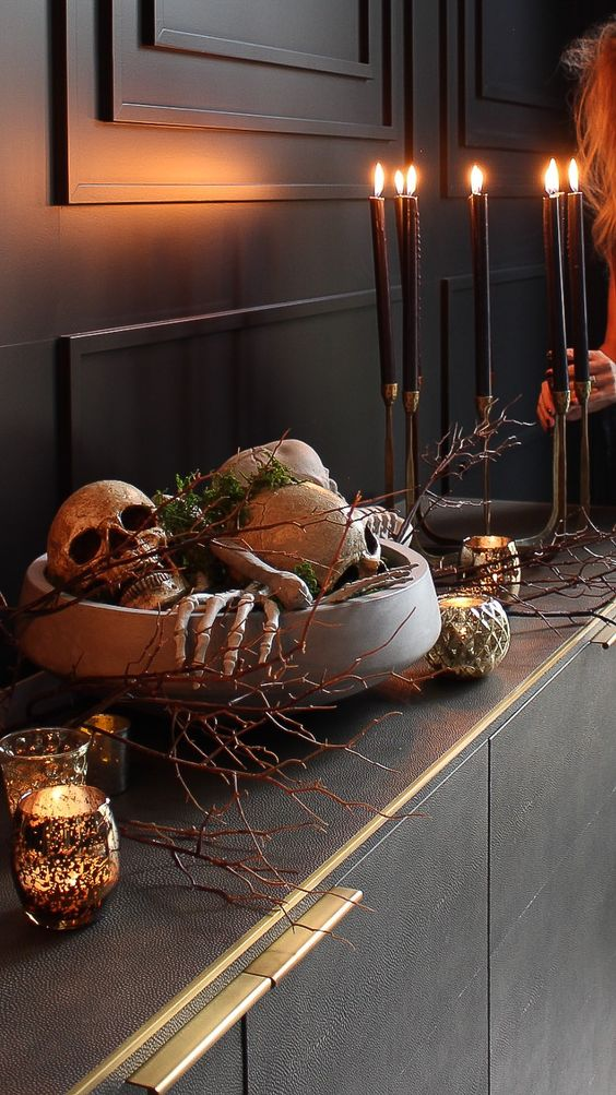 refined Halloween decor with a bowl filled with skeleton hands, skulls and moss, branches, candles around is amazing