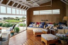 rolled up garage doors open up a countryside living room to the outdoor spaces and make it filled with fresh air and provide cool views