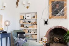 simple and stylish Halloween decor with a portrait covered with spiderweb, black and white pumpkins and a giant spider is cool