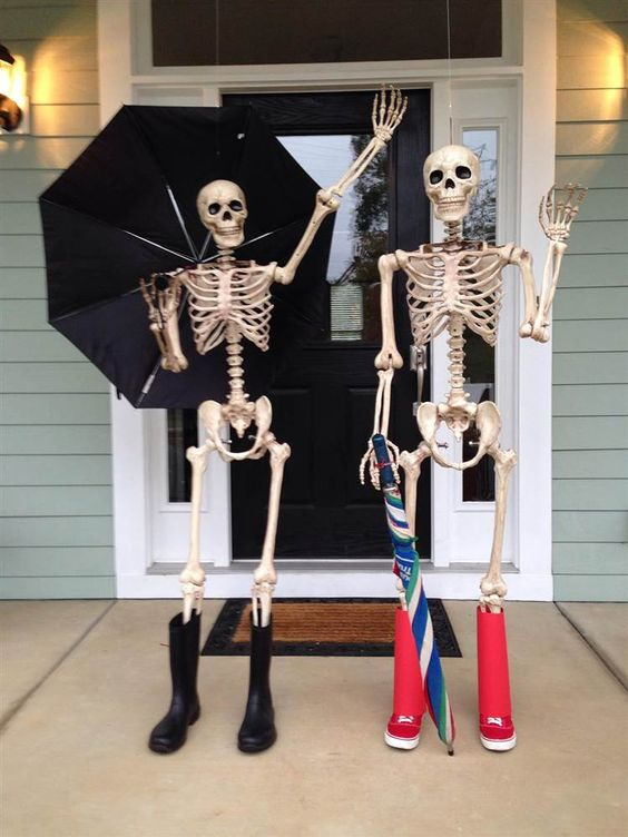 skeletons dressed in rubber boots, with an umbrella are great to rock on your Halloween porch