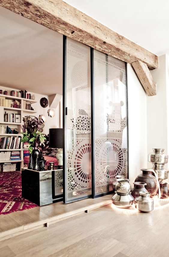 sliding glass doors covered with lace screens to support for a relaxed boho feel in the space are a very creative and cool solution