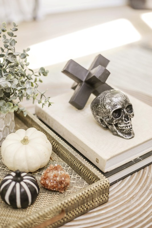 style your coffee table with a skull and a couple of pretty black and white pumpkins for modern Halloween decor