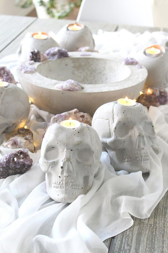 stylish concrete skull candleholders paired with geodes are gorgeous for modern Halloween decor and you cna DIY them