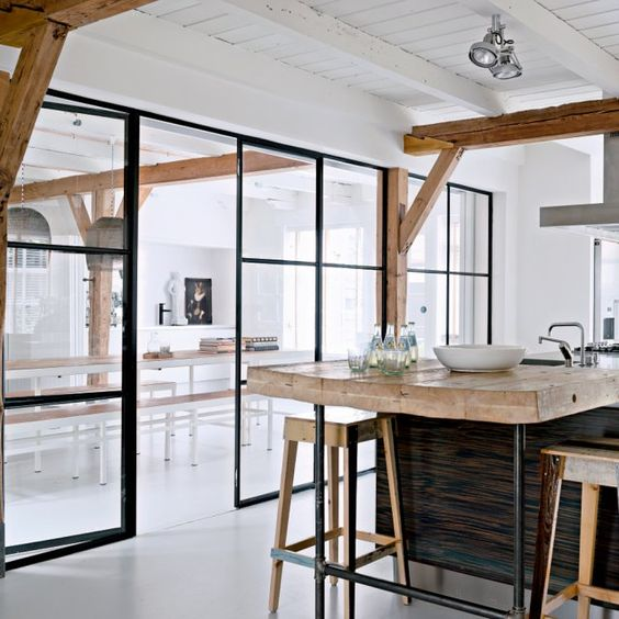 the kitchen and dining room divided with a framed glass wall with a door is a great idea to separate the space but do it gently