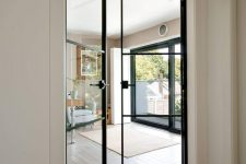 very delicate black metal frame glass doors with black handles are amazing to separate the living room from the rest of the house and let light in and out
