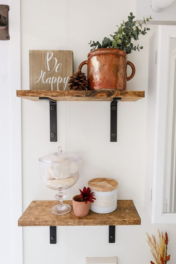 wooden shelves, a sign, a copper pot with eucalyptus, some soaps in a jar and a bloom make up a pretty fall arrangement
