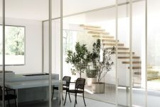 zoning the open layout with glass walls and white frame glass sliding doors in them is a cool way to separate the spaces