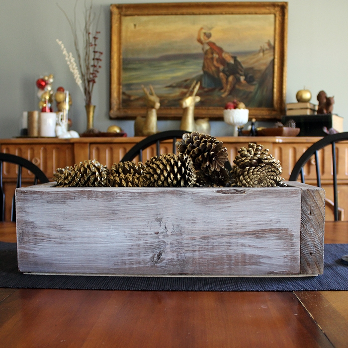 wooden box with pinecones centerpiece