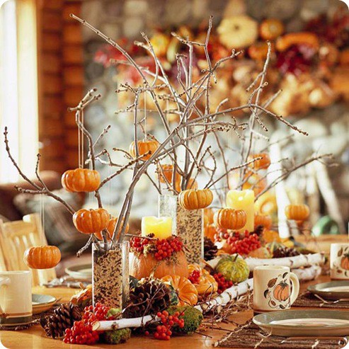 For easy fall's arrangements grab a bunch of vases, stuff dried twigs in them and hang cute little pumpkins on these twigs.
