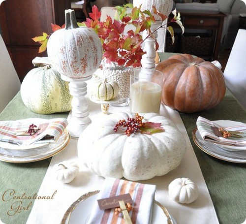 To create sophisticated ambience, spray paint several pumpkins in white and use them as background for more traditional autumn's decorations, like berries, fallen leaves and so on.