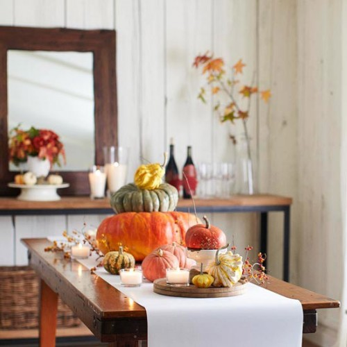 Keeping high objects on one end and draped table runner down the other, creates the effect of a waterfall. Btw, stacked pumpkins works well as for porch decorating as for different indoor arrangements.