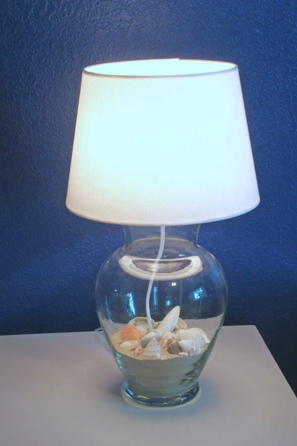 glass vase lamp filled with sand and shells