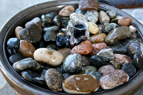 A Small patio handmade fountain with beautiful sea stones. A large ceramic pot and a plastic bucket would be needed for the project. (via shelterness)