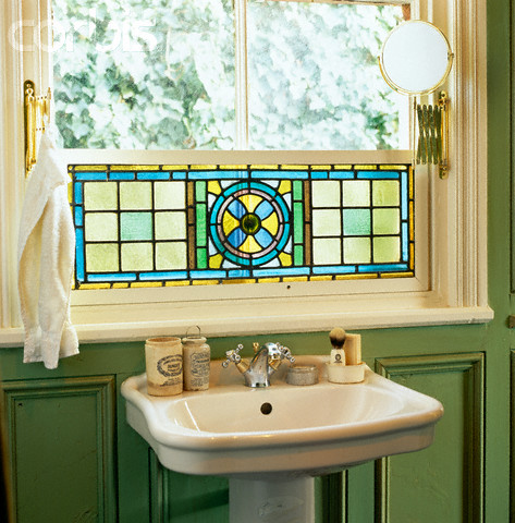 sink under a stained glass window in a green bathroom shelterness