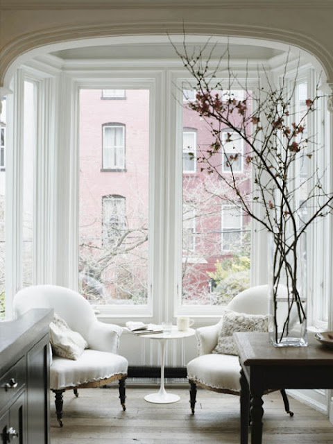 a table in front of two comfy chairs provides a nice place to get a cup - Bay Window Design Ideas