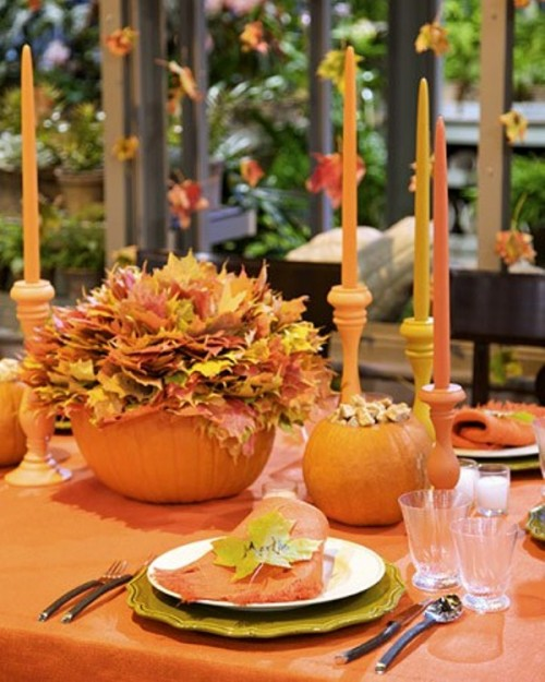 a brigth fall table setting with an orange tablecloth, bright candles, bold fall leaves and pumpkins