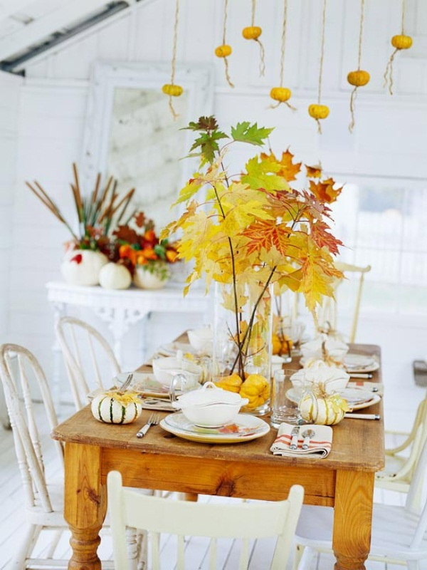 a neutral fall table with bright fall leaves in vases, natural pumpkins and neutral and stripes linens looks cool