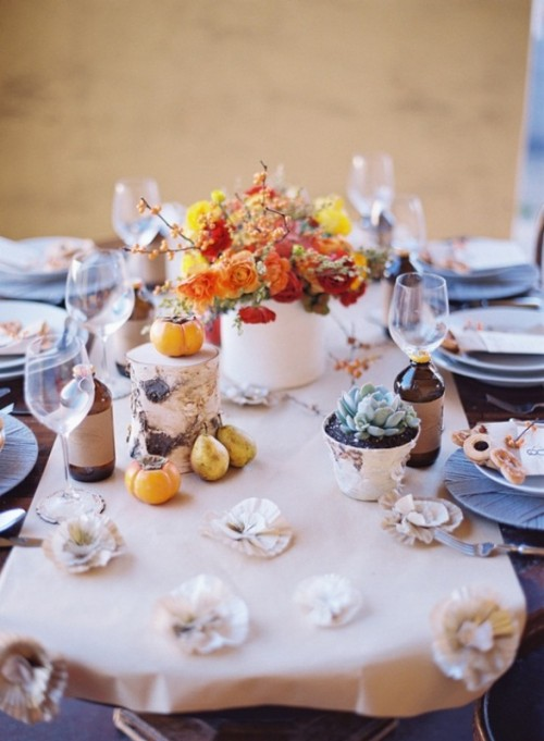 an elegant fall tablescape with neutral linens, bright blooms, fruits and veggies and a potted succulent plus porcelain