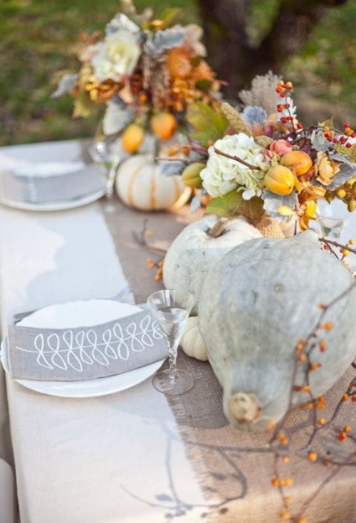 a beautiful fall table setting with neutral linens, real pale pumpkins, blooms, berries, fruits and printed napkins