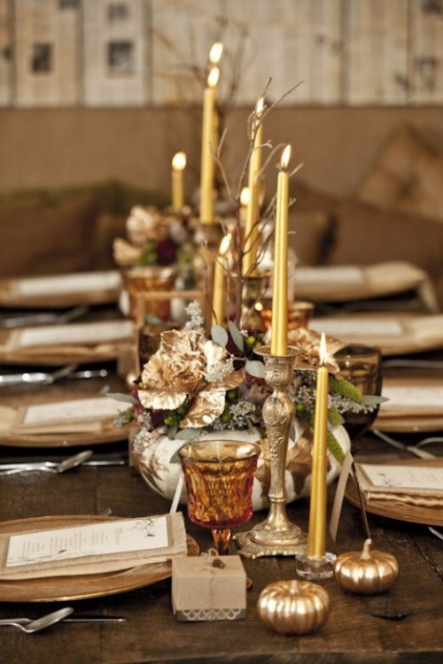 a chic fall tablescape with metallic chargers, candles, candleholders and faux pumpkins, leaves, greenery and other stuff