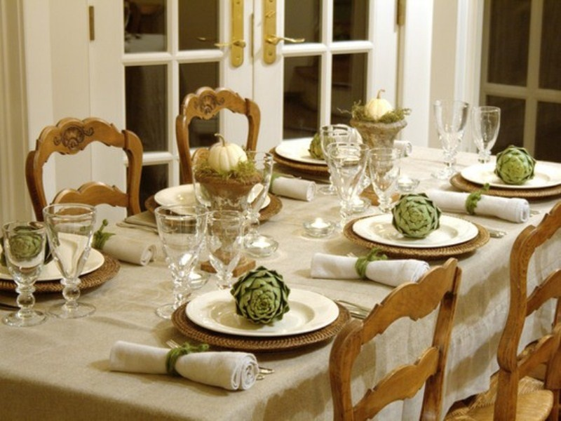 a vintage farmhouse fall tablescape with metallic chargers, neutral linens, artichokes, a white pumpkin and moss