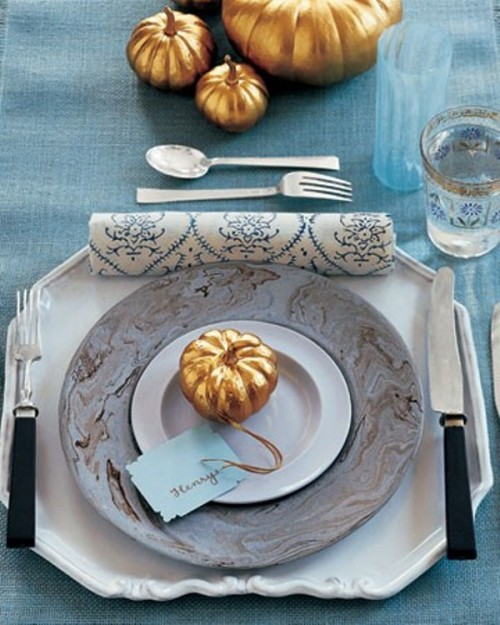 a chic fall tablescape with a blue tablecloth and a glass, a marble charger, faux gold pumpkins