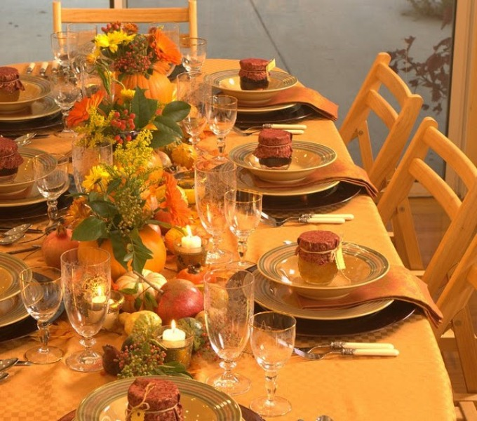 a bright fall table setting with bold and plaid linens, colorful candles and bold fall blooms and greenery in pumpkins