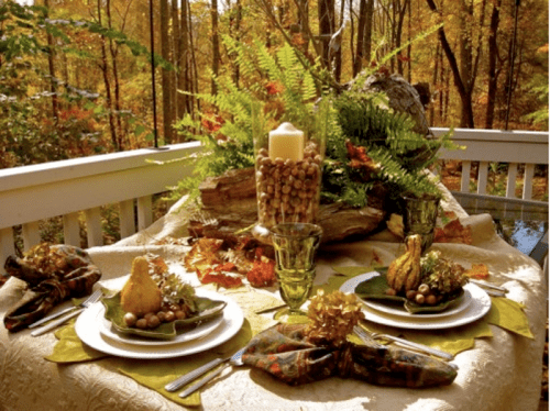 a woodland fall tablescape with neutral and printed linens, ferns, blooms, candles and nuts
