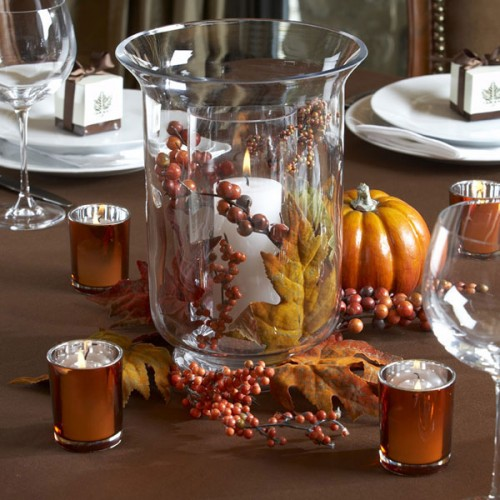 a chic fall centerpiece of a candle with faux leaves and berries, faux pumpkins and copper candleholders