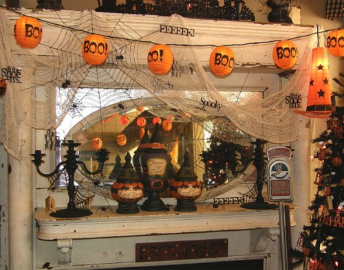 a messy Halloween mantel with spiderwebs, paper lanterns, black candleholders, lights and buntings