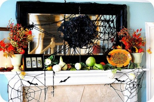 a Halloween mantel with spiderwebs, faux veggies and spiders, brigth fall blooms and leaves and a spider nest