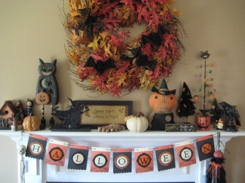 a vintage Halloween mantel with a faux leaf wreath, a vintage bunting, candles and vintage pumpkin toys