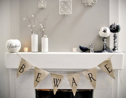 an elegant black and white Halloween mantel with black and white pumpkins, a burlap banner and a faux blackbird for a chic look