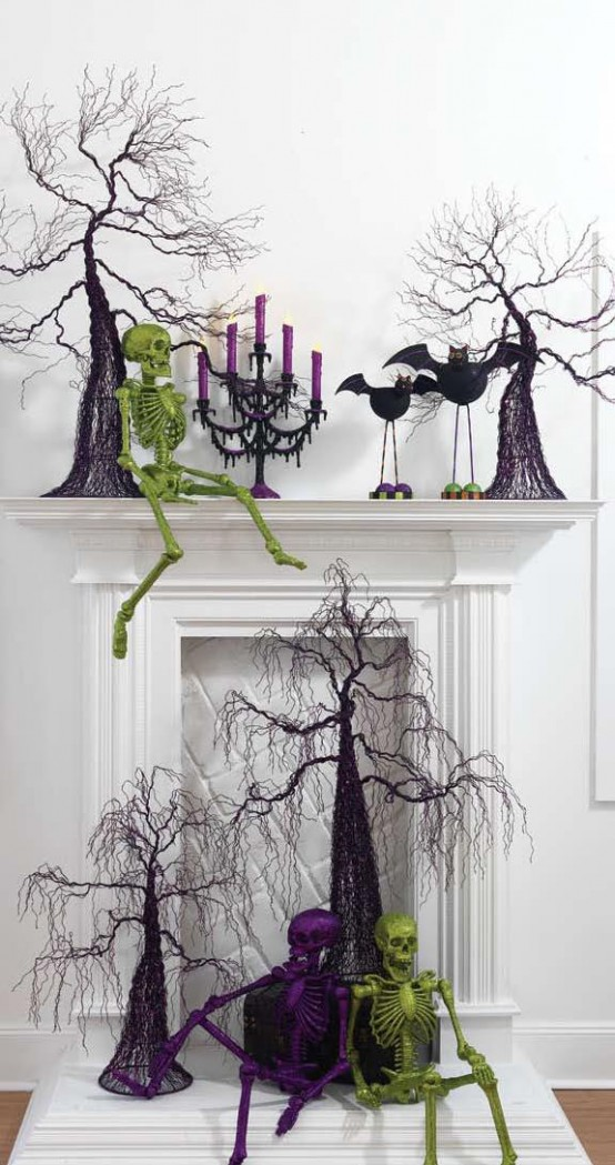 a bold Halloween mantel with a neon green skeleton, scary purple trees, purple candles and funny bats plus a scary tree and skeletons in front of the fireplace