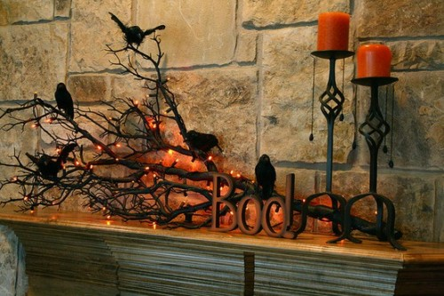 an elegant Halloween mantel with branches, lights, candles and faux blackbirds is very lovely decor