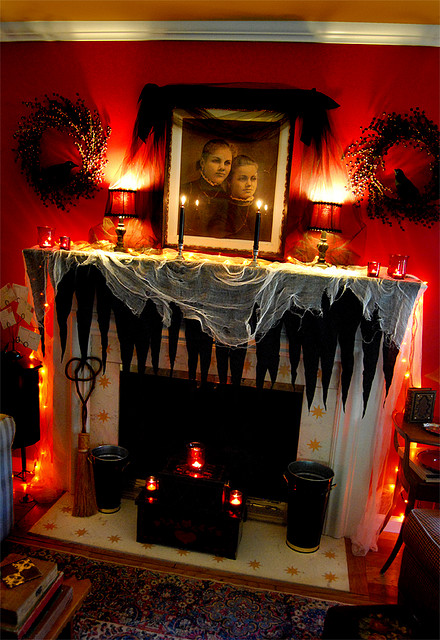 a scary Halloween mantel with spiderwebs, black icicles, black candles, red candleholders and lamps plus a scary photo
